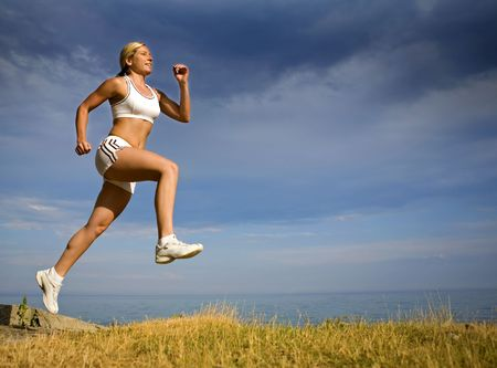 healthy athlete running on the beach in the summer
