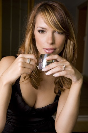 stunning woman holding cup of espresso looking away
