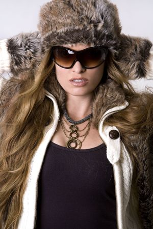 winter fashion: stunning woman wearing winter outfit with fur and glasses