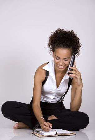 brunette woman using her phone on grey isolated background Stock Photo