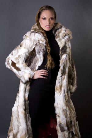 winter woman: pretty model wearing fur coat and black pants indoors