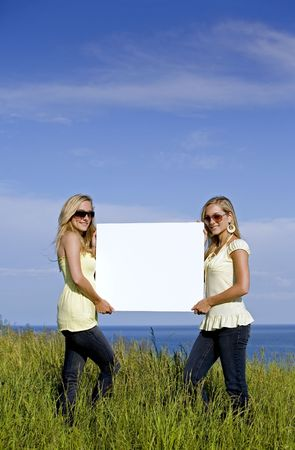sisters holding white sign in the summer day Stock Photo - 3187715