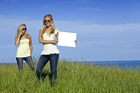 sisters holding white sign in the summer day Stock Photo - 3208903