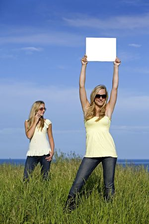 sisters holding white sign in the summer day Stock Photo - 3208899