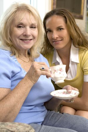 indoors: mother and daughter are enjoying coffee together indoors Stock Photo