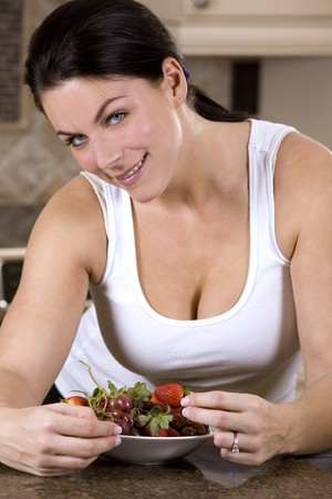 pretty brunette with strawberries in the home kitchen photo