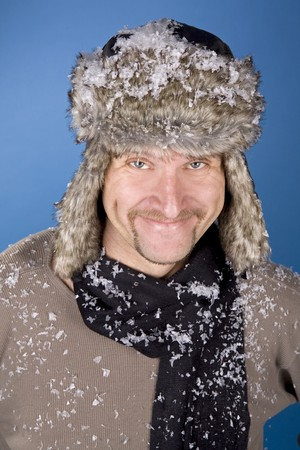 russian man: russian man wearing fur with snow on blue
