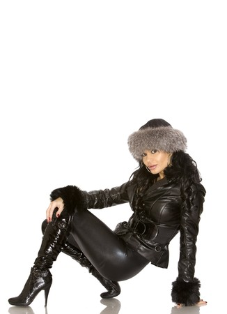 winter fashion: pretty model wearing leather outfit on white background