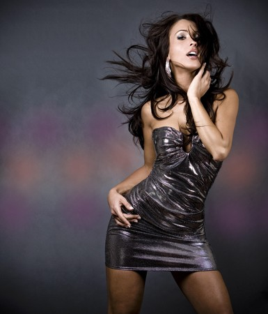 outfits: pretty brunette woman wearing dress on dark background Stock Photo
