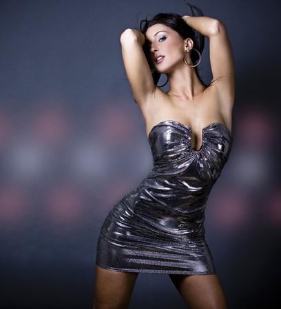 mooie brunette vrouw draagt jurk op donkere achtergrond