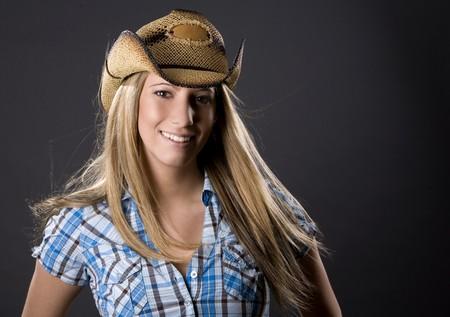 beautiful blond woman wearing cowboy outfit on grey photo