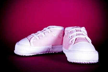 pair of pink baby shoes on dark background