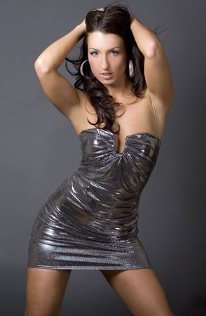 silver dress: pretty brunette woman wearing dress on dark background Stock Photo