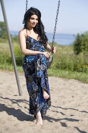 pretty brunette wearing summer long blue dress outdoors photo
