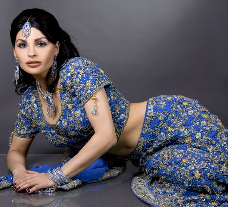 pretty brunette wearing traditional indian outfit on dark photo