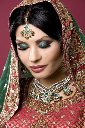 middle eastern clothes: beautiful indian woman wearing bridal outfit on white