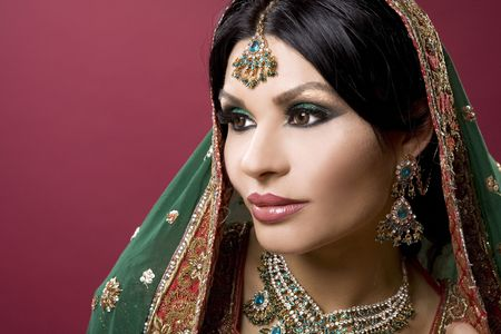 beautiful indian woman wearing bridal outfit on red
