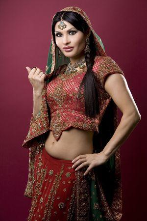 mooie Indiase vrouw met bruids-outfit op rode