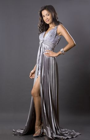 pretty brunette woman wearing silver dress on grey Stock Photo