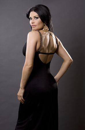 pretty brunette woman wearing black dress on grey photo