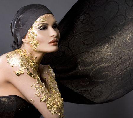 pretty brunette wearing gold outfit and matching makeup photo