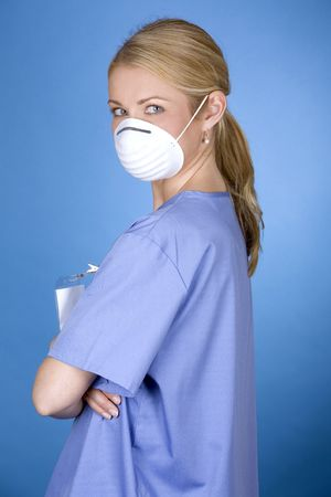 h1n1: blond healthcare worker wearing blue scrubs and mask