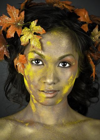 pretty brunette woman wearing leaves and colorful makeup photo