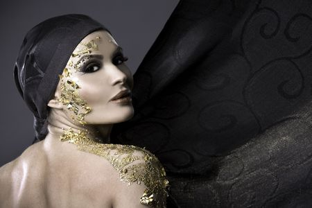 pretty brunette wearing gold outfit and matching makeup Archivio Fotografico