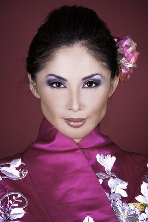 pretty asian woman wearing kimono on red background