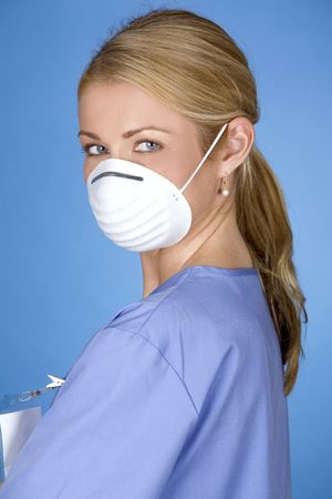 blond healthcare worker wearing blue scrubs and mask