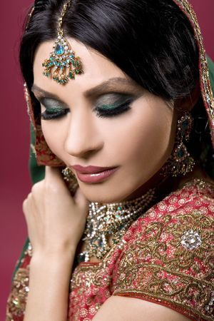 beautiful indian woman wearing bridal outfit on red photo
