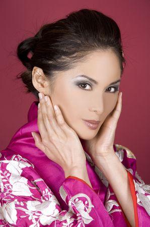 pretty asian woman wearing kimono on red background photo