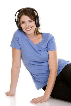 pretty casual brunette is listening to music on white background Stock Photo
