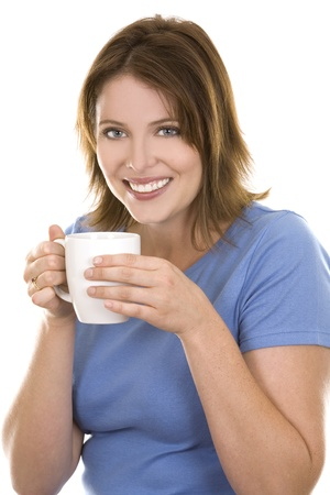 women holding cup: pretty casual brunette wearing blue top holding cup of coffee