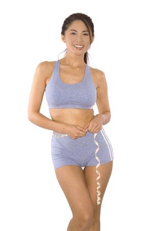 pretty asian woman measuring her waist line photo