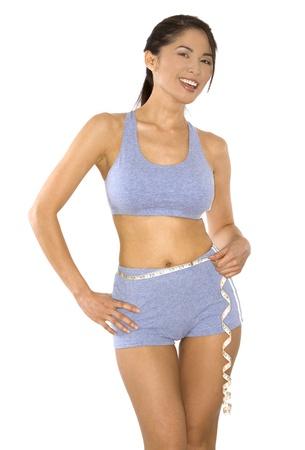 Mujer bastante asiática medir su línea de cintura Foto de archivo - 10382621