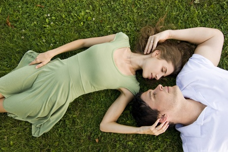 couple in the park relaxing on their backs photo