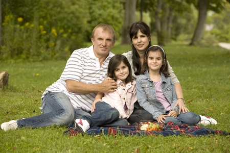 family of four outdoors having picnic in the grass photo