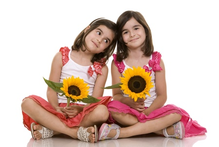 pretty brunettes twins sitting on white isolated background photo