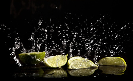 clear water splash with limes on black background photo