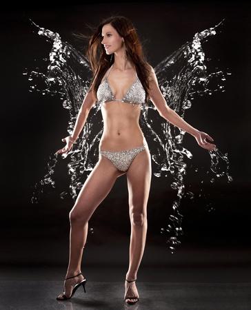 silver background: pretty brunette wearing silver bikini on black background Stock Photo
