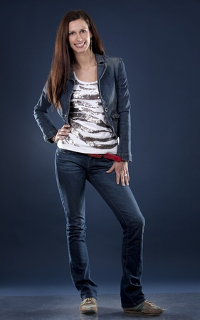 attractive gorgeous: pretty casual brunette on dark blue background Stock Photo