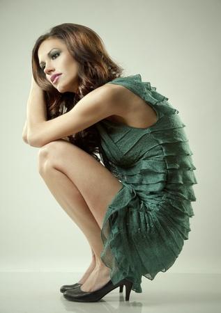 pretty brunette wearing green fashion dress on light background Stock Photo - 12478146