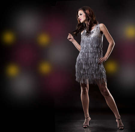 pretty brunette wearing silver party dress on black background Stock Photo - 12478129