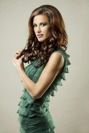 pretty brunette wearing green fashion dress on light background Stock Photo - 12478171