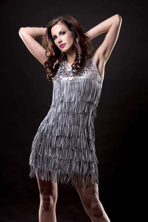 pretty brunette wearing silver party dress on black background Reklamní fotografie