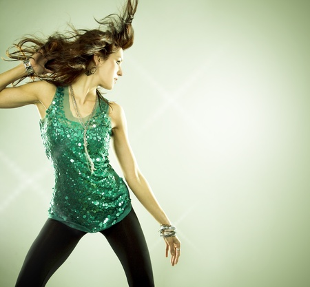 pretty brunette wearing green outfit on light background