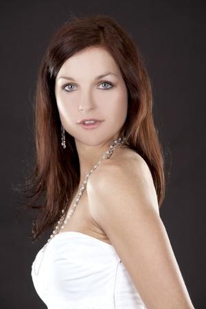 pretty brunette wearing white fashion dress on black background Stock Photo - 12908398