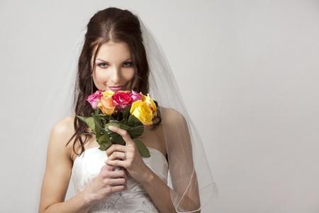 hübsche Brünette trägt Hochzeitskleid auf hellem Hintergrund