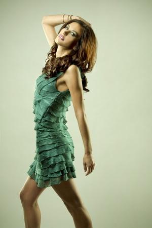 pretty brunette wearing green fashion dress on light background photo